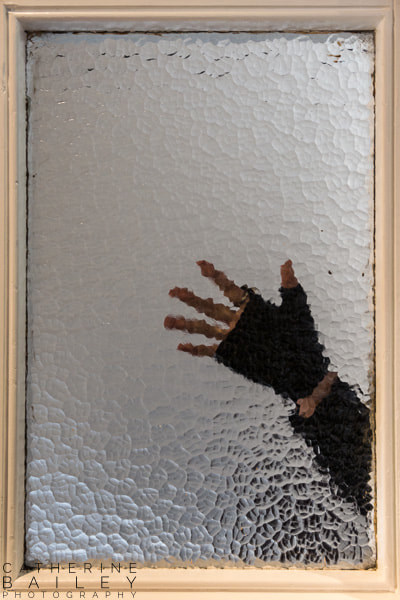 Gloved hand behind glass window | Catherine Bailey Photography