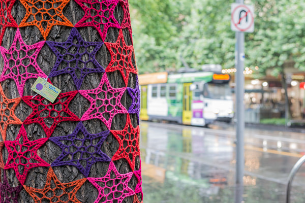 Yarn bombed tree and tram on Swanston St.