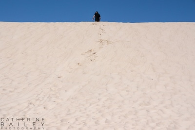 Man running up a sand dune | Catherine Bailey Photography