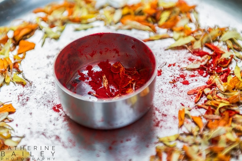 Spices in dish surrounded by marigold petals | Catherine Bailey Photography