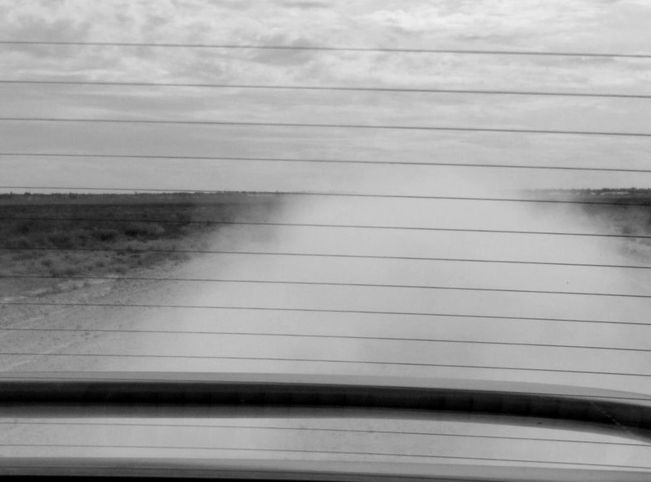 Dust on dirt road from back of car window | Catherine Bailey Photography